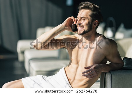 Handsome, young man talking on his cell phone in the morning in a hotel room with towel wrapped around his waist - stock photo