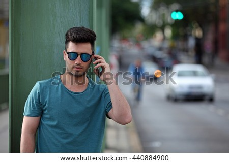 Handsome young man talking on mobile phone on the street