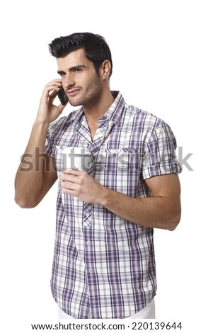 Handsome young man talking on mobilephone, drinking coffee, looking away. - stock photo