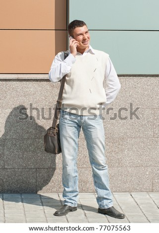 Handsome young man talking on the phone outdoors - stock photo