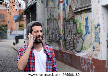 Handsome young man talking on the phone. Trendy and urban scene. - stock photo