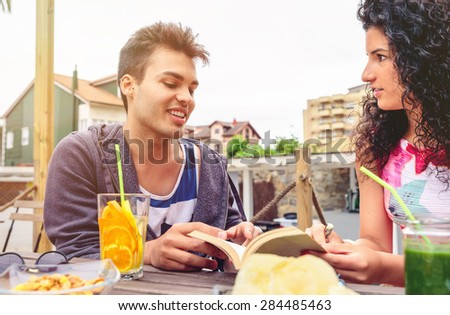 Handsome young man talking with a friend around the table with healthy drinks in a leisure summer day outdoors