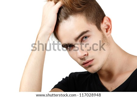 Handsome young man touching his hair, portrait of sexy guy looking at camera over white background - stock photo