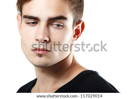 Handsome young man touching his hair, portrait of sexy guy looking down at corner over white background - stock photo