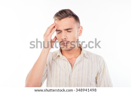 Handsome young man touching his head with one hand feeling strong headache - stock photo