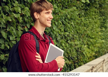 handsome young man using tablet computer. student with a backpack