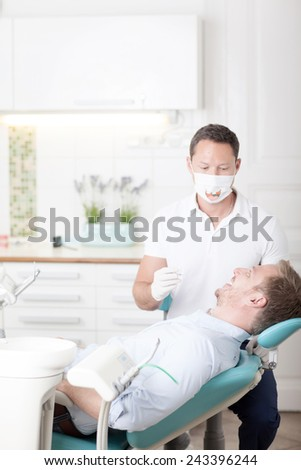 Handsome young man visiting dentist for dental checkup  - stock photo