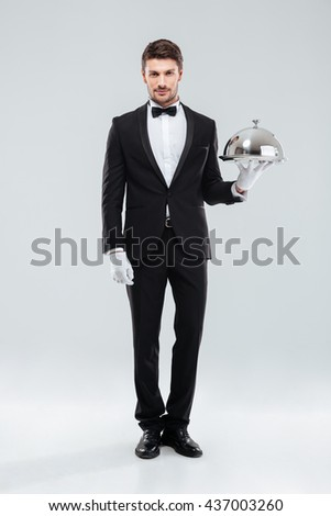 Handsome young man waiter standing and holding tray and lid over white background - stock photo