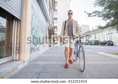Handsome young man walking down the street with his bicycle beside him. He is wearing a bag. - stock photo