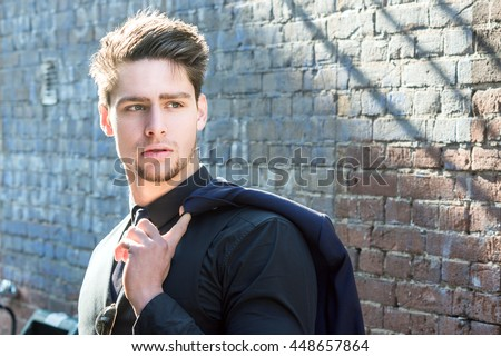 Handsome young man walking in an urban street with his suit jacket slung over his shoulder as he looks away, close up upper body view. Attractive male hipster model.