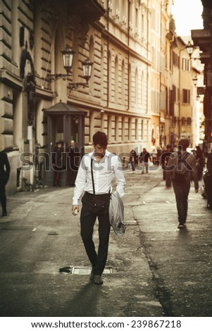 Handsome young man walking in European city street, an alley in Rome, Italy - stock photo