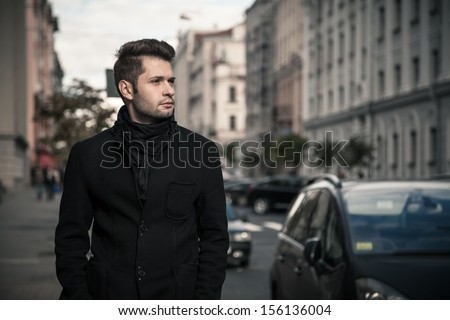 handsome young man walking on a street - stock photo