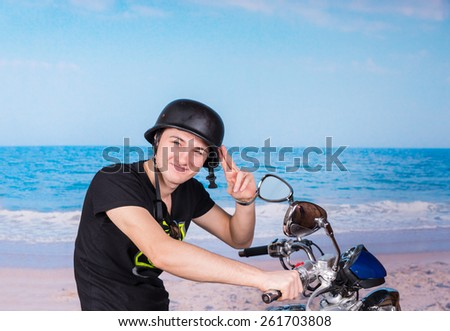 Handsome young man wearing an old-fashioned helmet saluting on his motorbike as he spends a relaxing day at the seaside - stock photo