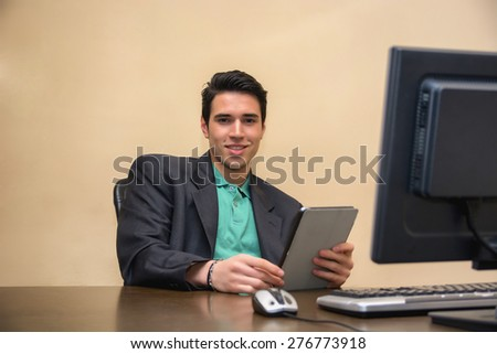 Handsome young man wearing business suit in office with tablet PC looking at camera, smiling.