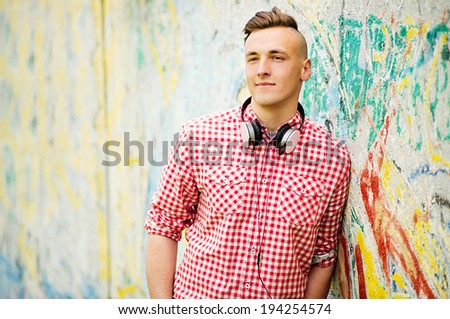Handsome young man wearing headphones slung around his neck looking at the camera with a pensive speculative expression - stock photo