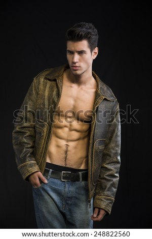 Handsome young man wearing leather jacket on naked torso, isolated on black background looking away