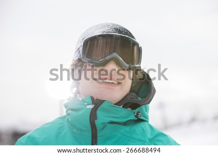 Handsome young man wearing ski goggles outdoors - stock photo