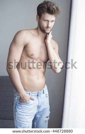 Handsome young man well-built stands at the window in the apartment - stock photo