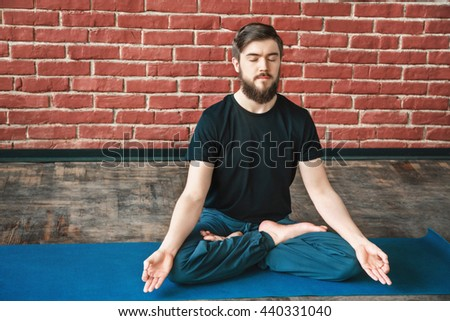 Handsome young man with a beard and closed eyes wearing black T-shirt doing yoga position on blue matt at wall background, copy space, lotus asana, portrait, meditation - stock photo
