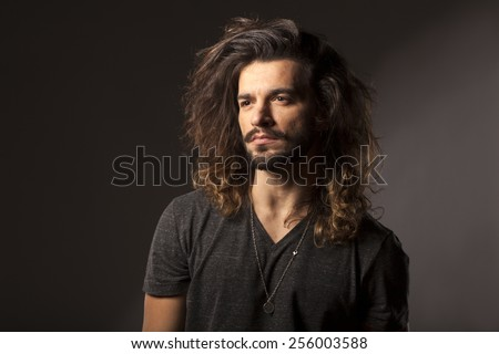handsome young man with a beard and long hair - stock photo