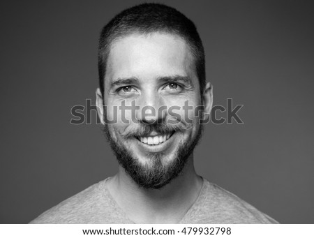 Handsome young man with a beard and mustache smiling broadly, gray background, black and white