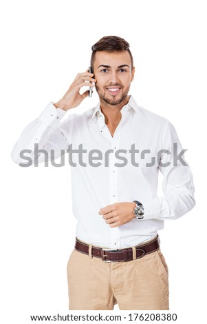 Handsome young man with a beard standing reading a text message on his mobile phone and smiling with pleasure, three quarter pose on white