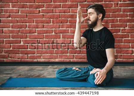 Handsome young man with a beard wearing black T-shirt doing yoga position on blue matt at wall background, copy space, portrait, pranayama exercises. - stock photo