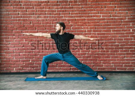 Handsome young man with a beard wearing black T-shirt doing yoga warrior position on blue matt at wall background, copy space, virabhadrasana. - stock photo