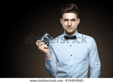Handsome young man with a camera in his hands. Photographer's work. Festive photo. Photos creativity - stock photo