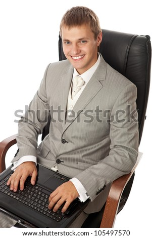Handsome young man with a laptop sitting in an armchair - stock photo