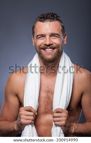 Handsome young man with beard is standing and smiling. His torso is naked. The man is holding white towel over his neck and smiling. Isolated on grey background - stock photo