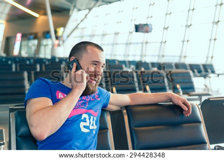 handsome young man with blond short hair talking on the phone, sitting on a chair with things at the airport waiting for his flight - stock photo