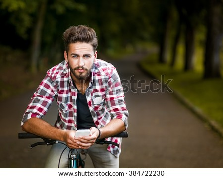 Handsome young man with blue eyes stops cycling, to check his smart phone looking at the camera in an alley with green trees - stock photo