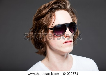 Handsome young man with brown long hair and sunglasses isolated on grey background. Fashion studio shot.