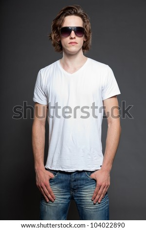 Handsome young man with brown long hair and sunglasses isolated on grey background. Fashion studio shot. - stock photo