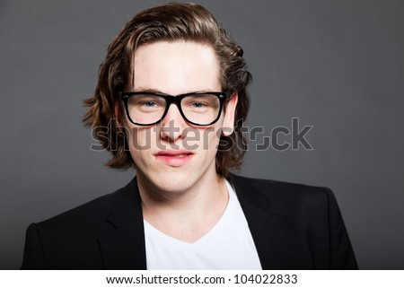 Handsome young man with brown long hair and wearing white shirt and blue jacket and retro glasses isolated on grey background. Fashion studio shot. Expressive face.