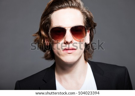 Handsome young man with brown long hair and wearing white shirt and blue jacket and sunglasses isolated on grey background. Fashion studio shot. Expressive face.
