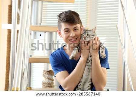 Handsome young man with cute cat sitting on steps at home