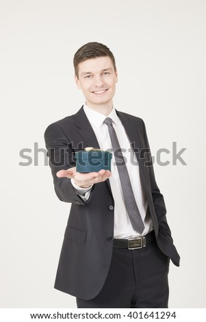 Handsome young  man with gift box on the grey background. - stock photo