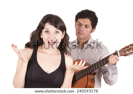 handsome young man with guitar serenading surprised beautiful girl isolated on white