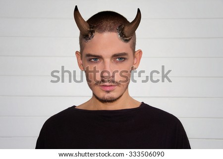 Handsome young man with halloween horns and blue eyes in black t-shirts - stock photo