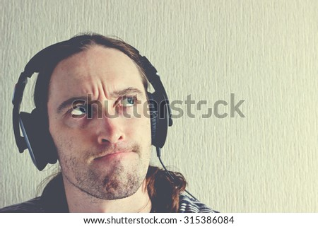 Handsome young man with headphones thinking about music. Image with vintage effect filter - stock photo