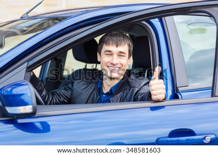 Handsome young man with his thumb up sitting in his new car