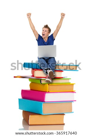 Handsome young man with laptop sitting on stack of books isolated on white