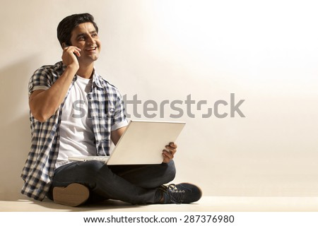 Handsome young man with laptop talking on cell phone - stock photo