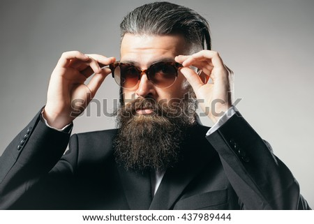 Handsome young man with long beard and moustache in black jacket in fashionable sun glasses in studio on grey background