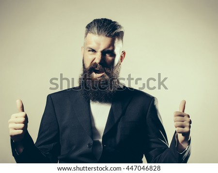 Handsome young man with long beard and moustache on screaming face in black jacket with super gesture in studio on grey background