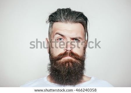 handsome young man with long beard and moustache on serious face with raised eyebrow on grey background in studio