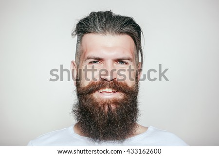 handsome young man with long beard and moustache on smiling happy face on grey background in studio
