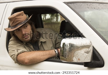 Handsome young man with long hair in brown cowboy hat driving white 4x4 car after rain. Safari style.